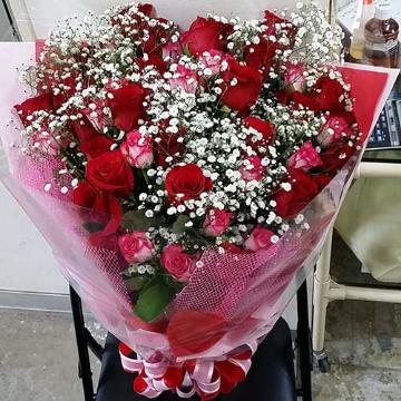鮮やかなバラとかすみ草の花束